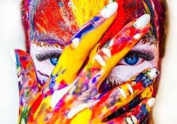 A close up on a female face streaked with a variety of different colored paints, her hand (also covered) is over her face but her fingers are split so her eyes are visible.