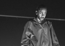 A black and white photo of Kendrick Lamar in performance, his eyes closed