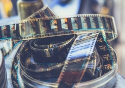 A coil of motion picture film is coming uncoiled