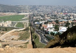 A photo of the border between the United States and Mexico showing sparse population on the US side and signs of high density populations on the Mexican side
