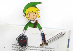 A paper cutout of Link from the Legend of Zelda peeking up from the top of a book