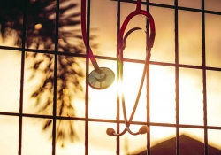 A photograph of a stethoscope hanging into a window through which the sun is shining
