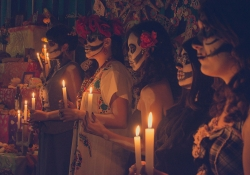 A group of people with their faces painted white like skulls hold candles before an altar