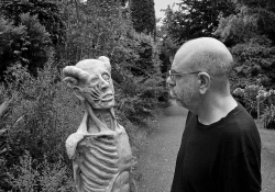 A black and white photograph of Dimitris Lyacos, who is standing on a road running down a wooded lane. He is looking at a grotesque statue that looks like a human with its skin removed.