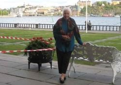 A photograph of an older woman standing by a bench, which is itself beside a river