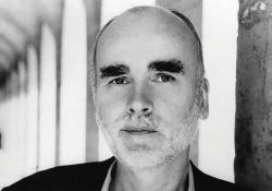 A black and white photograph of Adam Zagajewski. A row columns stretches out behind him
