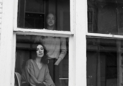 A black and white photo of a man, standing, and a woman, seated, looking through a window at the viewer