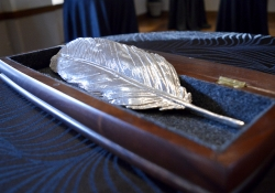 A feather, cast in silver, rests in a velvet lined box