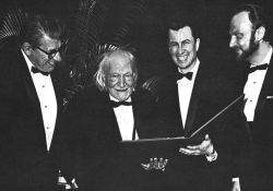 A black and white photo of four men standing in tuxedos