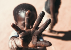 A photo of a young boy holding his hand up towards a camera, partially obscuring his own face