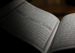 An open book written in Arabic, mostly shrouded in shadow