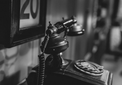A black and white photo of a vintage phone in a study