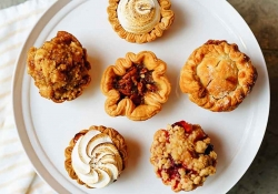 A photograph of six pastries on a white serving platter from above