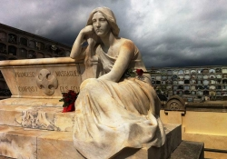 A statue of a reclining figure in a cemetery