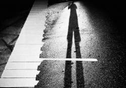 A black and photo of a long shadow cast across what looks like a piano keyboard