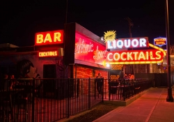 A desultory looking bar, decked with neon signs, presumably in Las Vegas