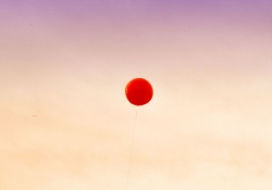 A red balloon hovers mid-frame against a dusking sky