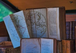 Two books standing but open in a library. One of them has a world map inset that is partially unfolded