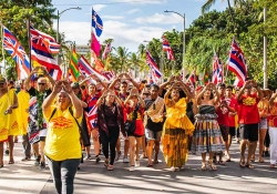 A group of people, clad in brightly colored clothes, march toward the camera waving the Hawai'ian flag