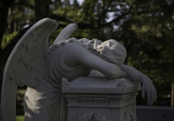 A sculpted angel throws herself across a grave in a show of grief