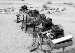 A black and white photograph of a line of typewriters on wooden desks on a beach. The desks and typewriters are covered with flotsam and sand.