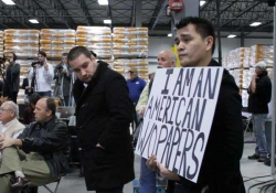 """Jose Antonio Vargas holds a sign at a Mitt Romney presidential campaign rally in 2011 in a scene from his film """"Documented."""" Photo courtesy of Apo Anak Productions."""