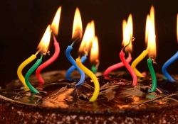 A photo of a chocolate birthday cake, its candles lit but strangely warped