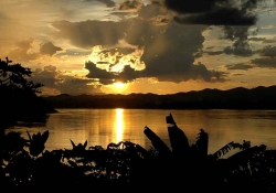 The sun sets on the opposite of the Mekong River