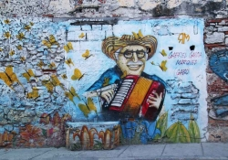 A photograph of a mural depicting a cartoonish drawing of Gabriel Garcia Marquez playing an accordion