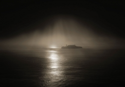 A sepia-toned photo of Alcatraz shrouded in fog