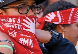A close photograph of a protestor, whose red bandana reads Missing and Murdered