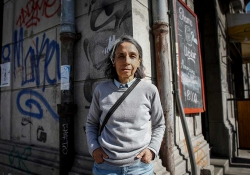 A photograph of Elvira Hernández standing in an urban landscape