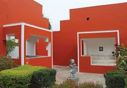 Two buildings, painted brightly red, intersect like angular puzzle pieces with a small green courtyard between them