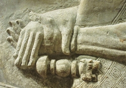 A bas-relief sculpture of hands clasping across the wrist