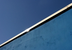 A photograph of the top of a border wall and the blue sky above