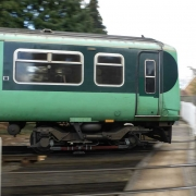 Green train passing platform outside