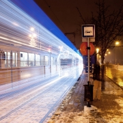 a tram in Hungary creates a streak of blue lights at night