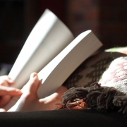 An open book in partial sunlight being held by a person with a blanket.