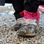 A refugee's shoes are worn, wet, and muddy after a long journey. These shoes are owned by Ali, a Yazidi refugee who traveled from Iraq to Preševo, Serbia, to avoid persecution (photo by Meabh Smith / Trócaire).